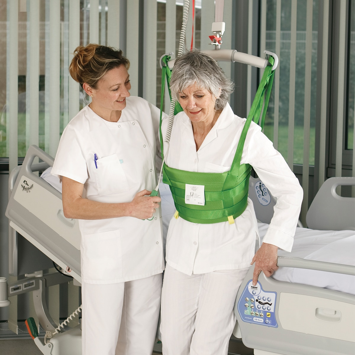 A clinician helps a patient walk in a hospital room with a Hillrom overhead lift and MasterVest